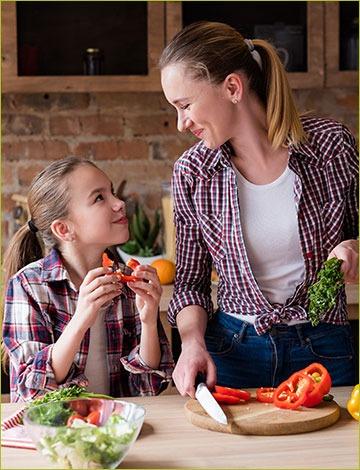 Woman and daughter prepare vegetarian meal